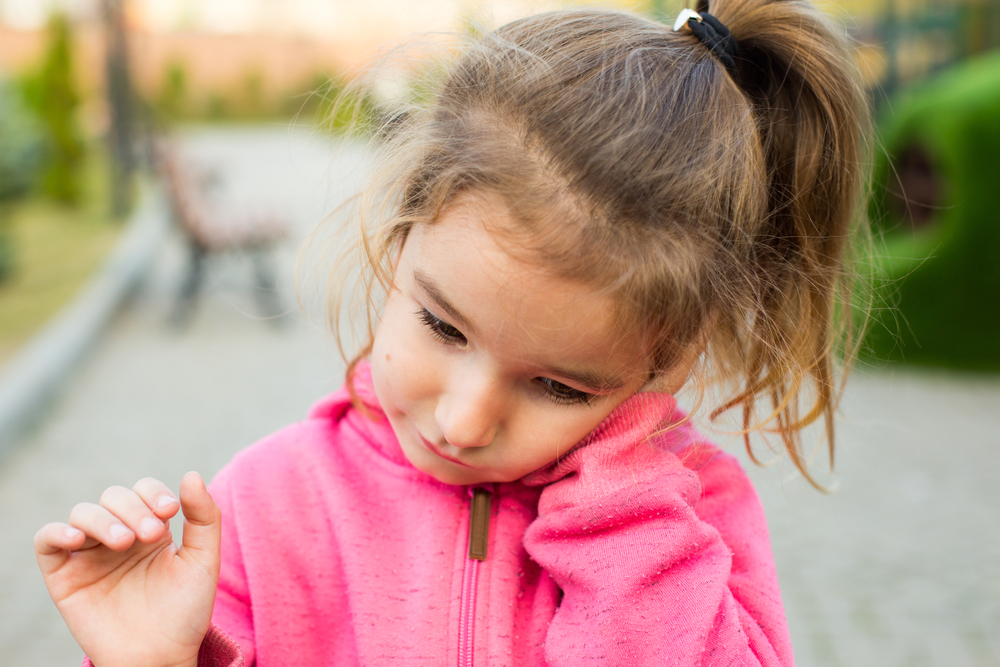little girl holding her sore ear, infection concept