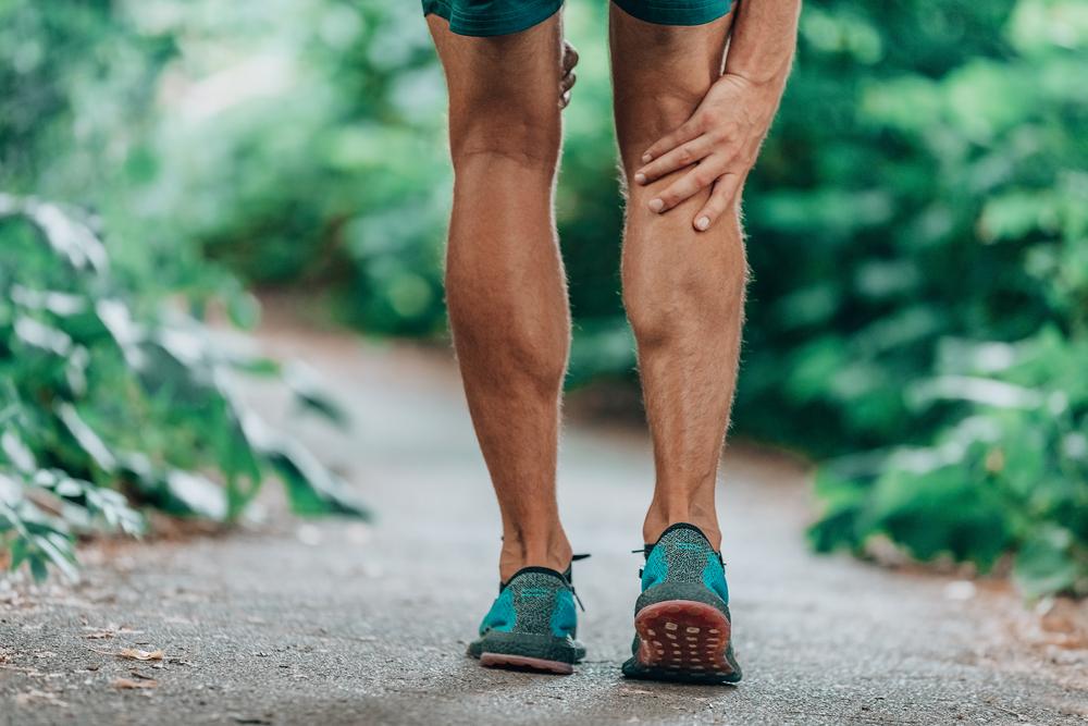 runner holding his calf, running pain