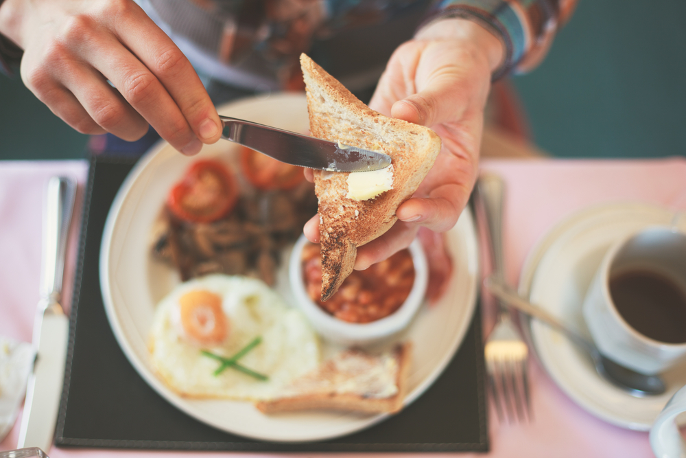 person buttering toast over a breakfast plate