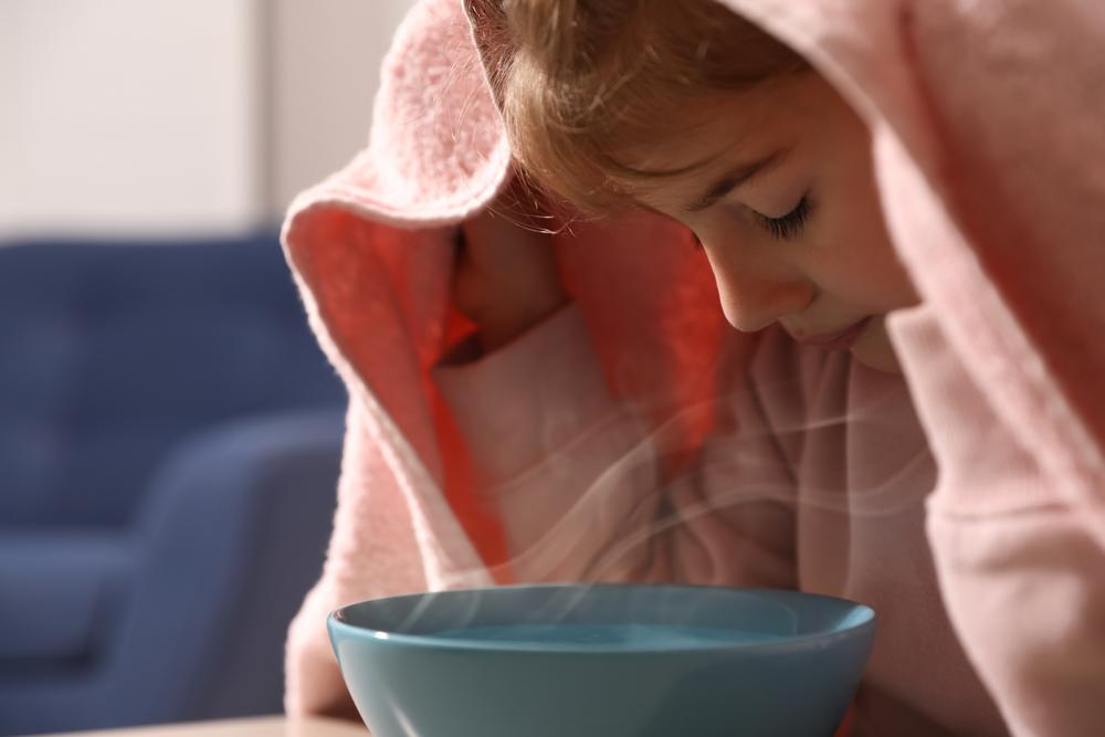 little girl breathing in steam for illness