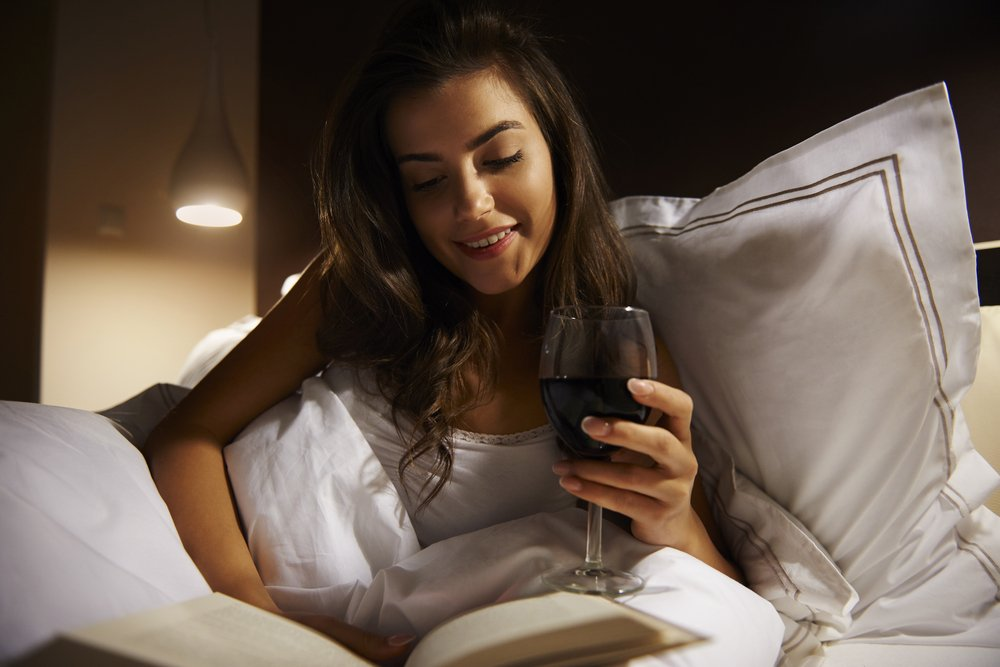 woman having wine in bed while reading