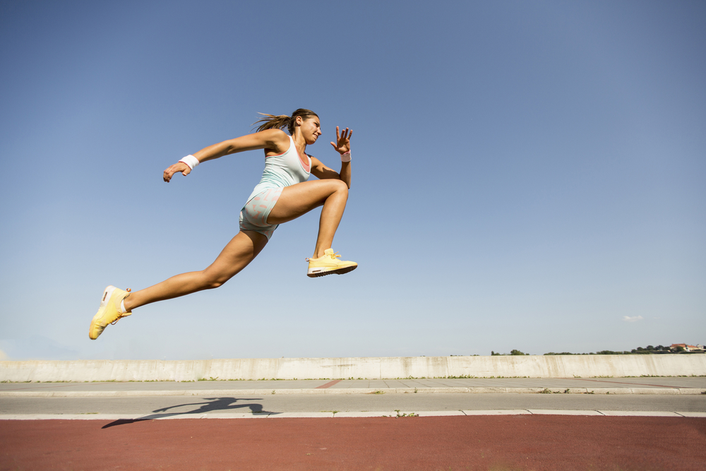 woman leaping on a running track