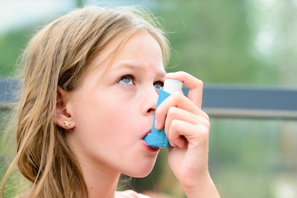 young girl using an asthma inhaler