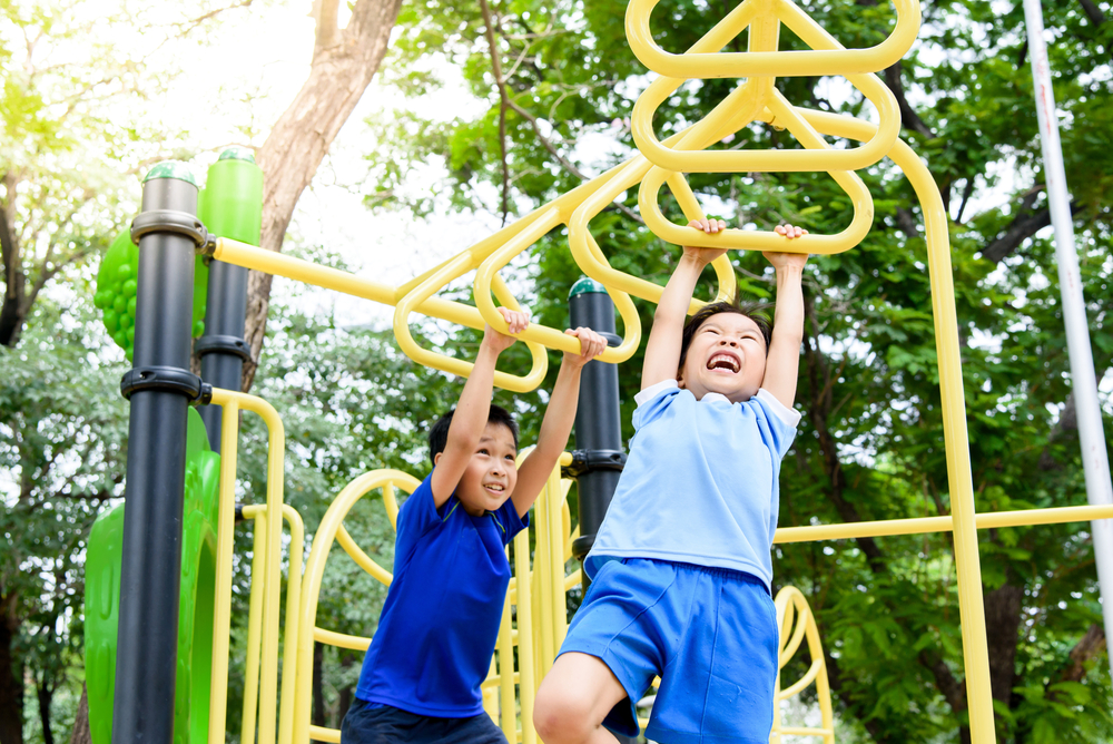 two little boys playing on jungle gym