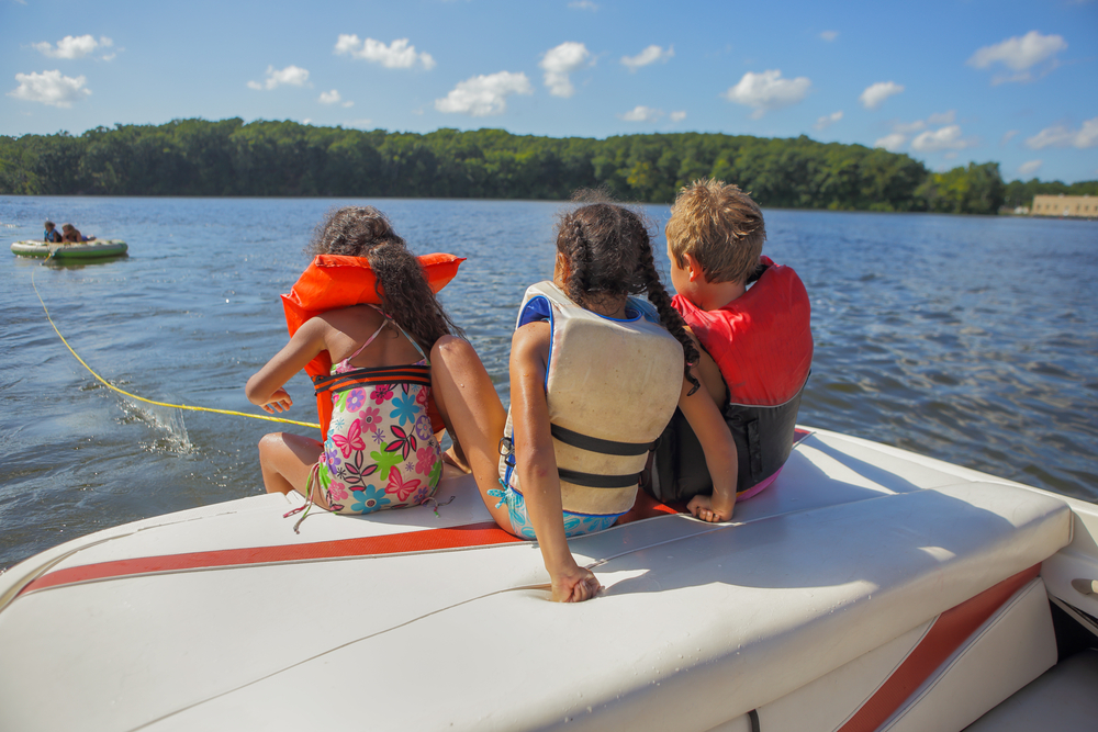 three kids with life jackets on a boat on a lake