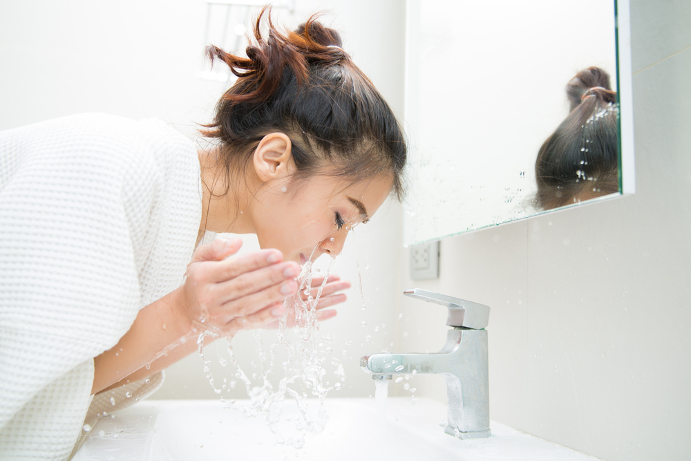 young woman splashing her face in bathroom