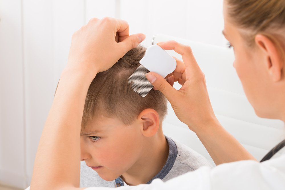 woman combing little boy's hair with a lice comb