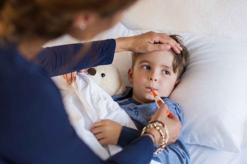 little boy sick in bed having temperature taken