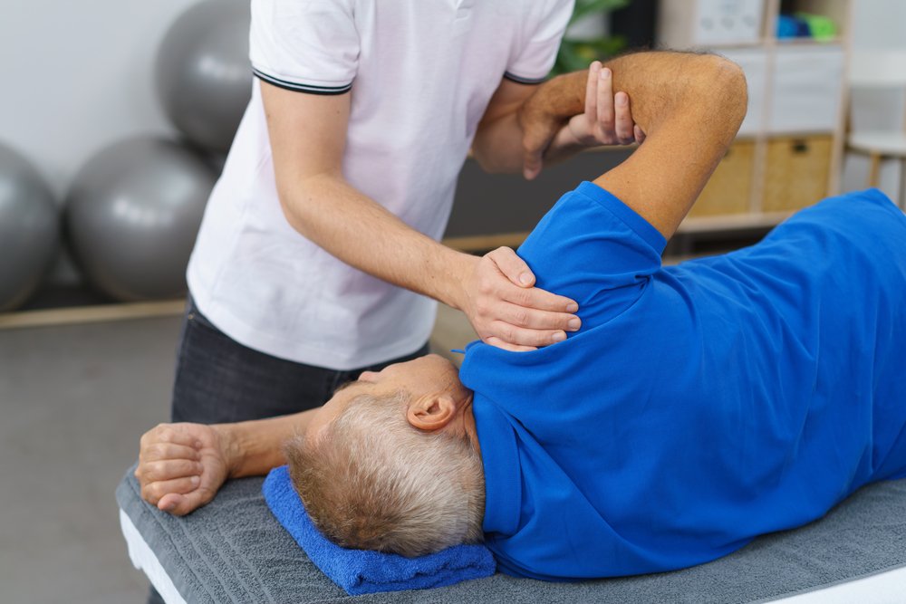 physical therapist working on patient's sore shoulder