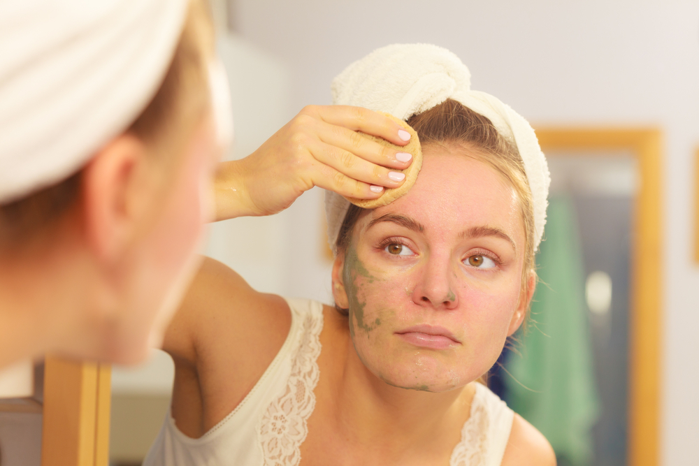 woman exfoliating her skin with a mask