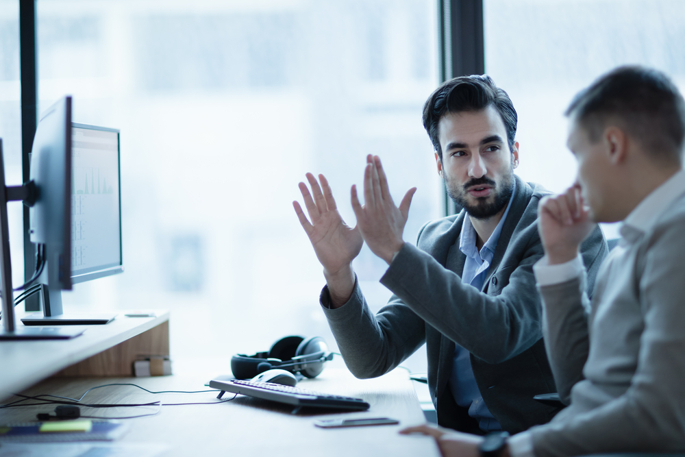 man explaining something to coworker in office