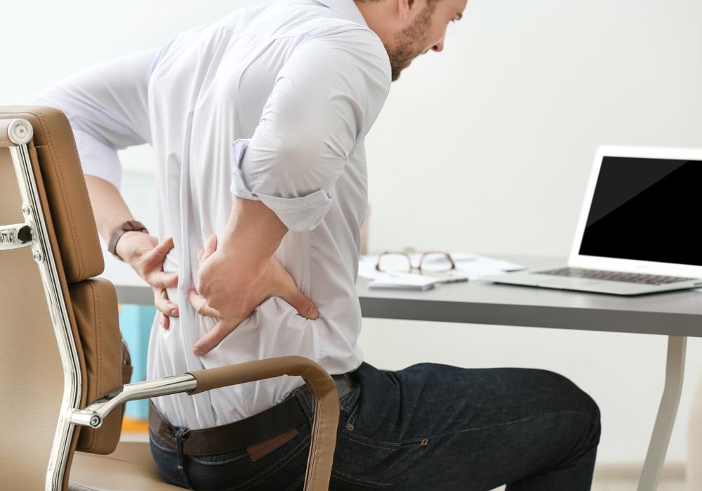 man at office desk feeling back pain