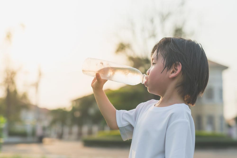 little boy drinking water outside, sweating from heat