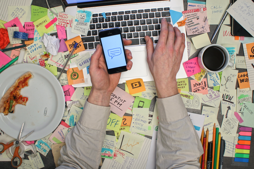 person with work addiction desk covered in sticky notes