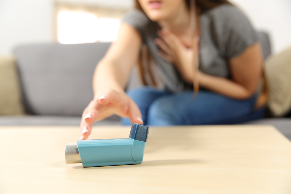 woman reaching for her inhaler; asthma attack