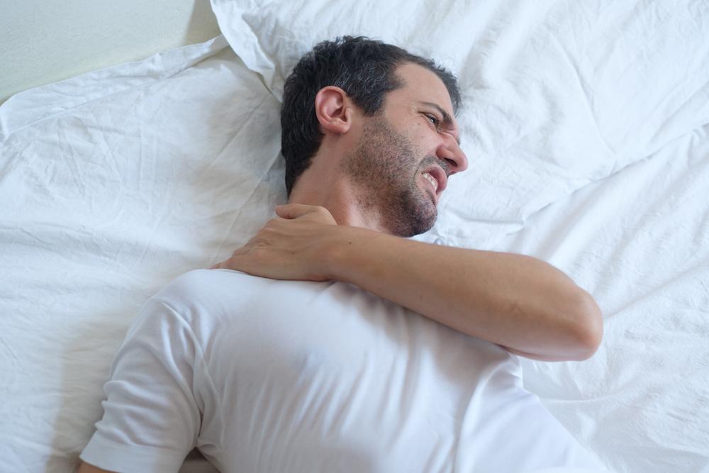 man lying down having neck or shoulder pain