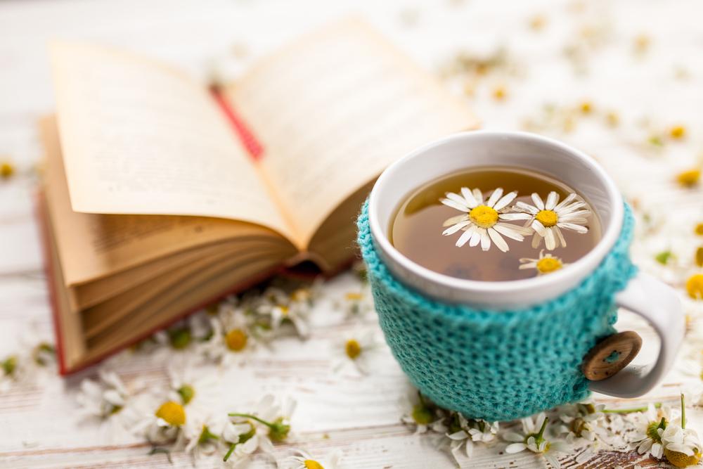 chamomile tea in a mug beside a book