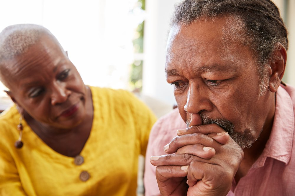 older man with depression is cared for by wife