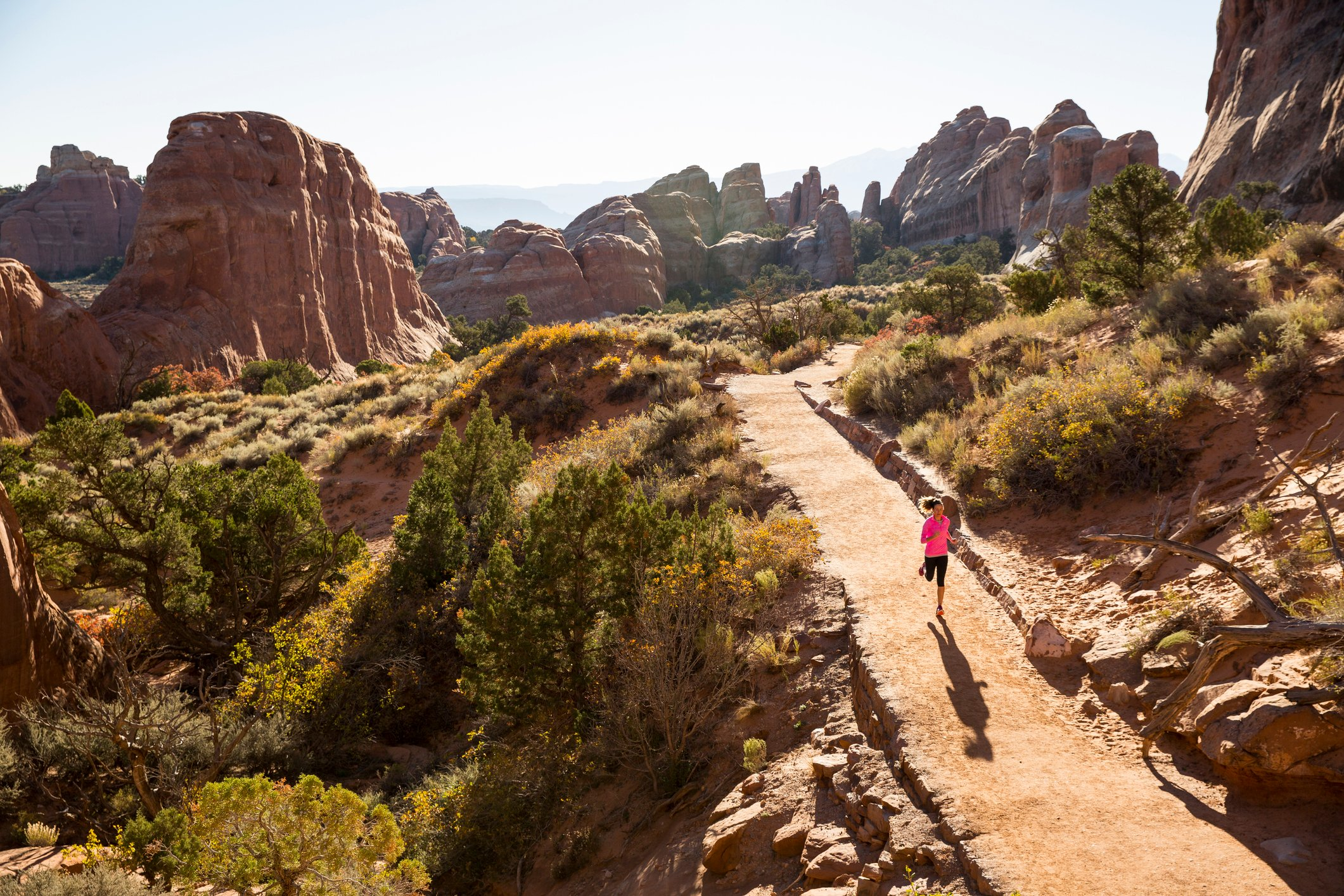 A woman trail running in Arches National Park.