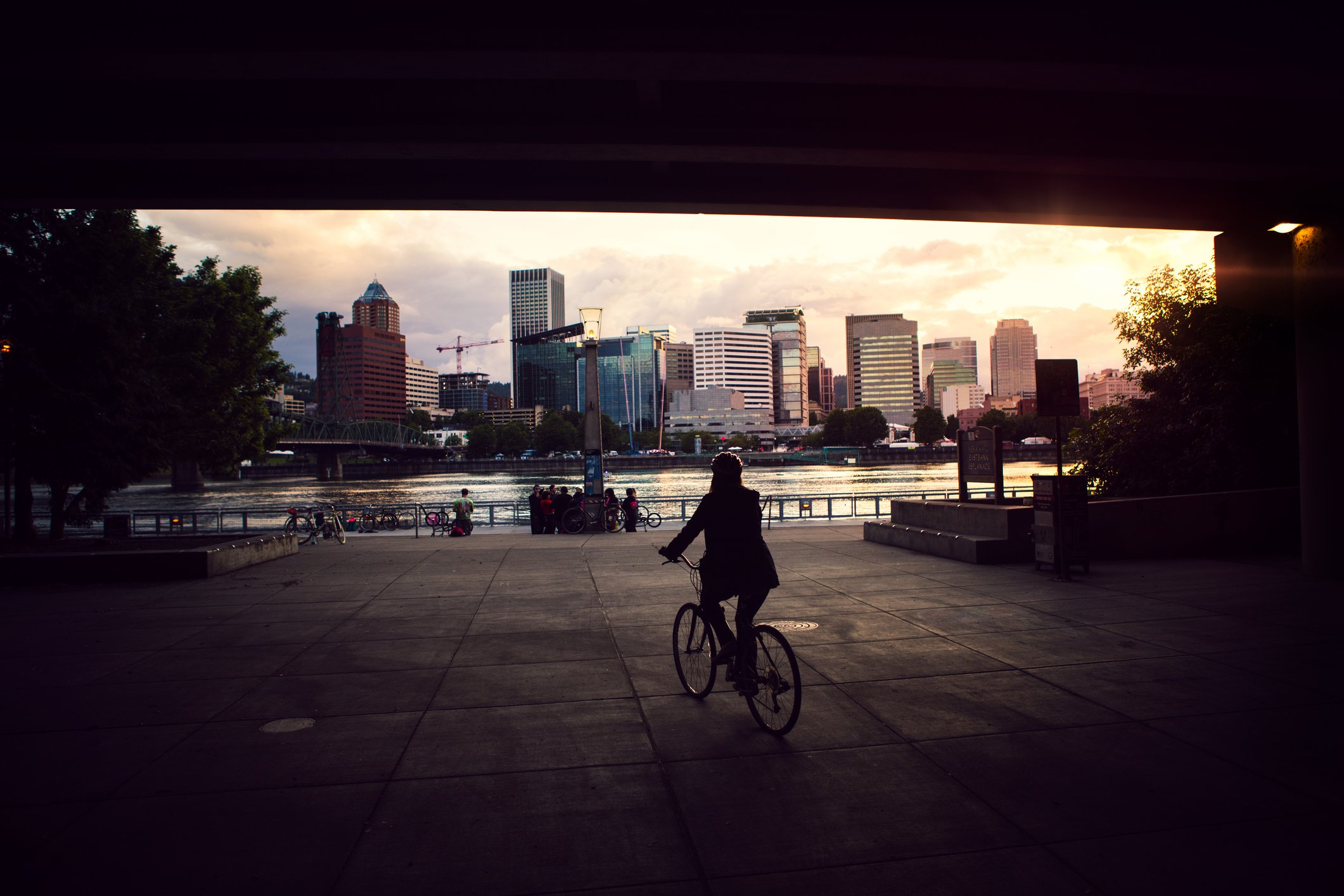 An adult woman rides her bicycle under a Interstate 5 overpass to the waterfront Eastbank Esplanade in Portland, Oregon. She is silhouetted by the bridges shadow, the city glowing orange in the setting sun.