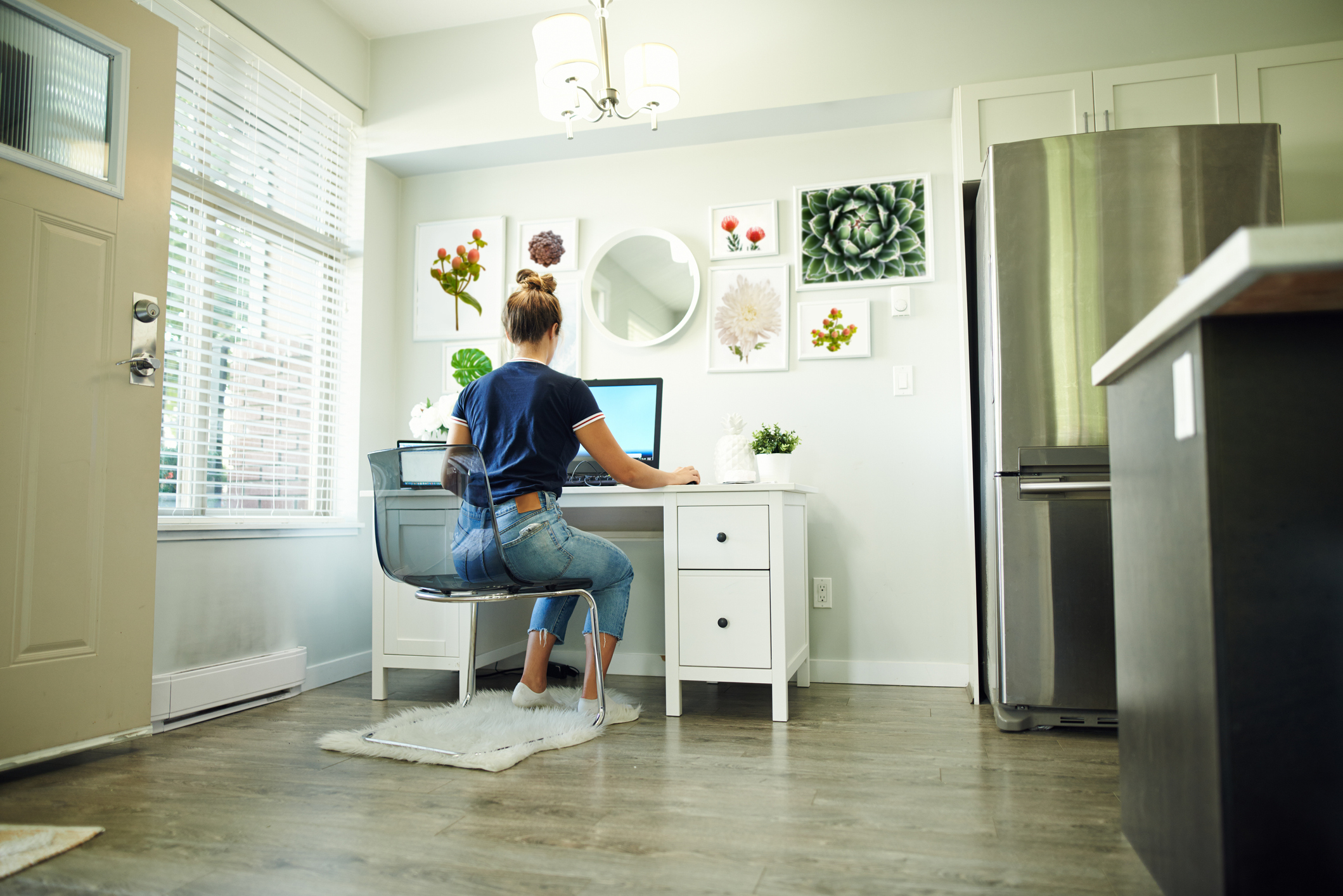 Rearview shot of a young woman using a computer while working from home