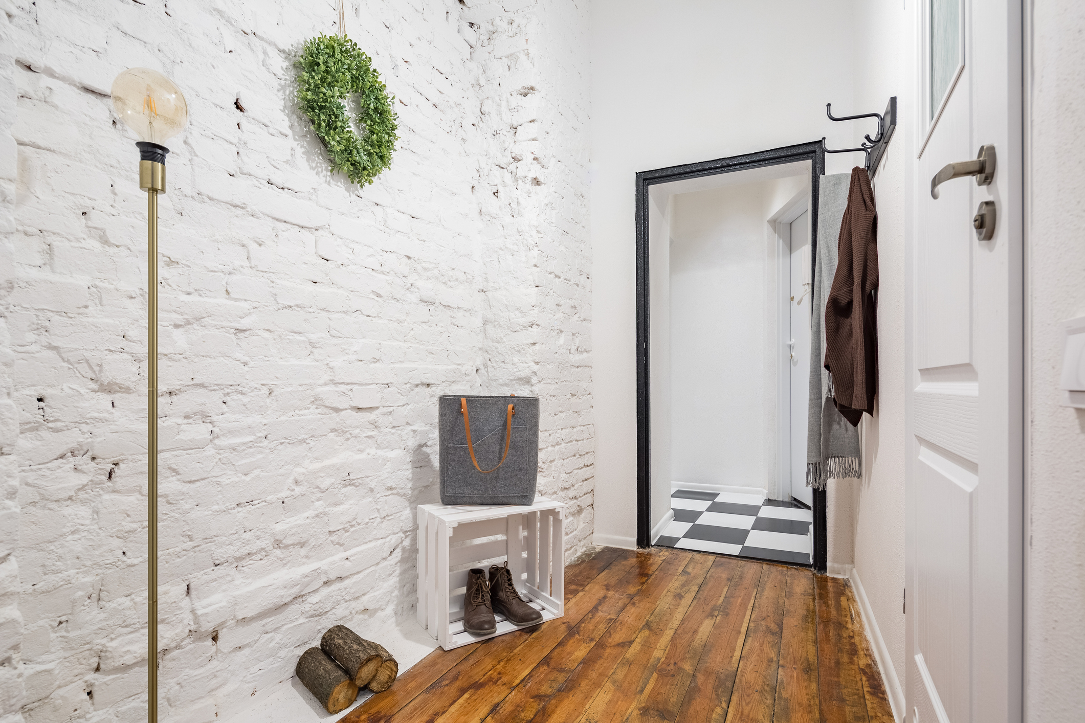 Industrial style mudroom with white brick wall and rustic hardwood flooring