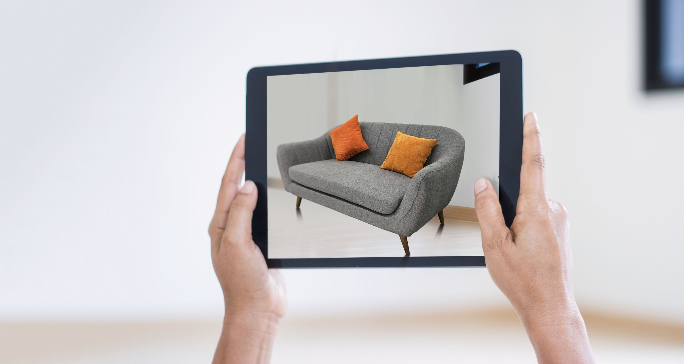 AR augmented reality. Hand holding digital tablet, AR application, simulate sofa furniture and and interior design real room background, modern technology.