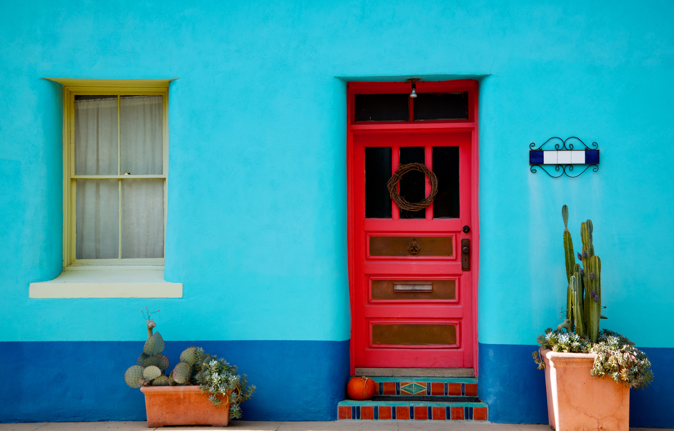 """""""Home in Arizona or Mexico showing turquoise blue stucco wall, red door and orange pumpkin. Door flanked by terracotta pots with local cacti."""""""