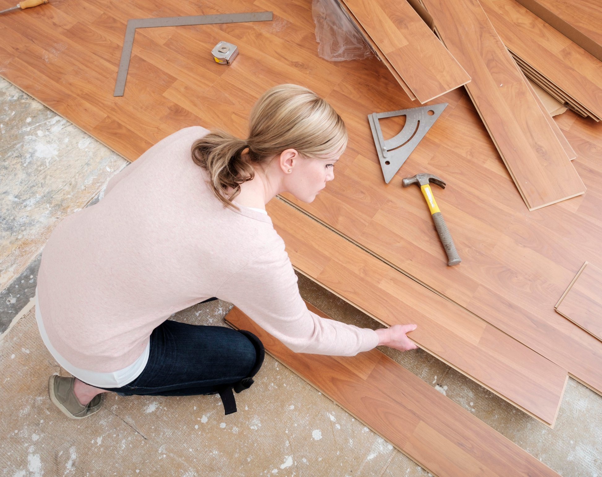 A woman working in her home on a do-it-yourself project installing laminate wood flooring. She is placing the board, as seen from above.