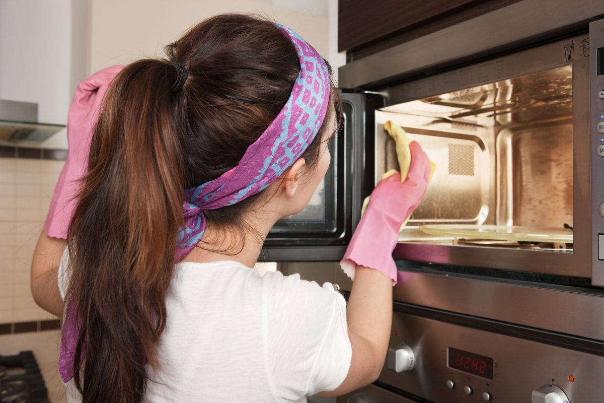 A woman cleaning a microwave