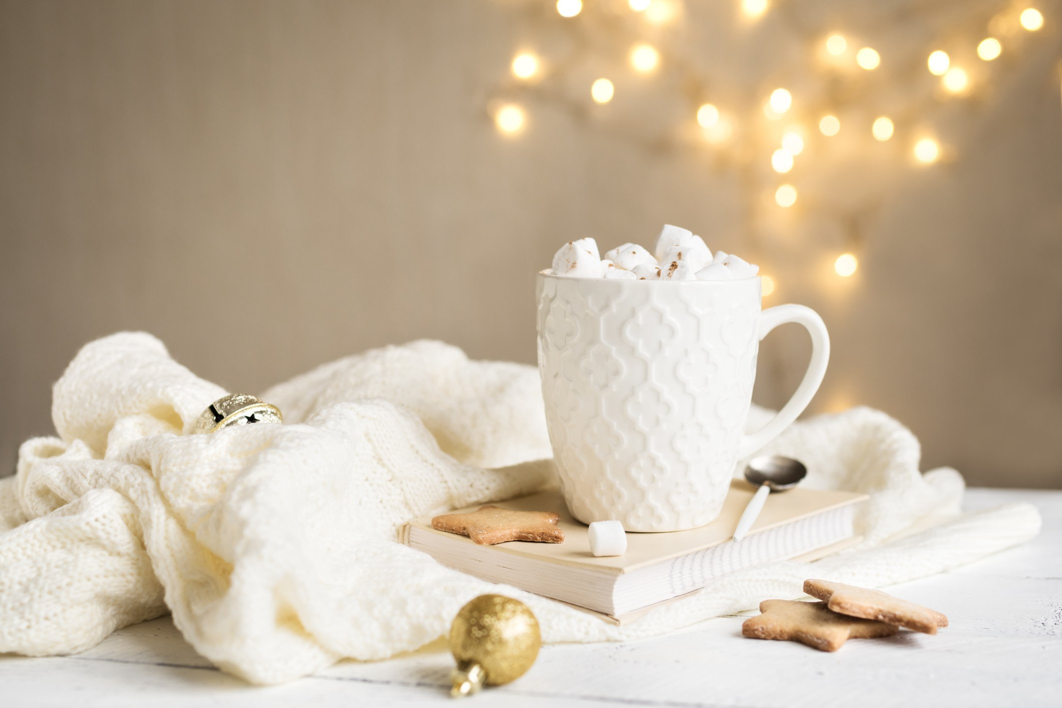 Christmas Hot chocolate with marshmallows in white mug, copy space. Hot cocoa drink for Christmas and winter holidays with warm scarf, lights, festive decor.