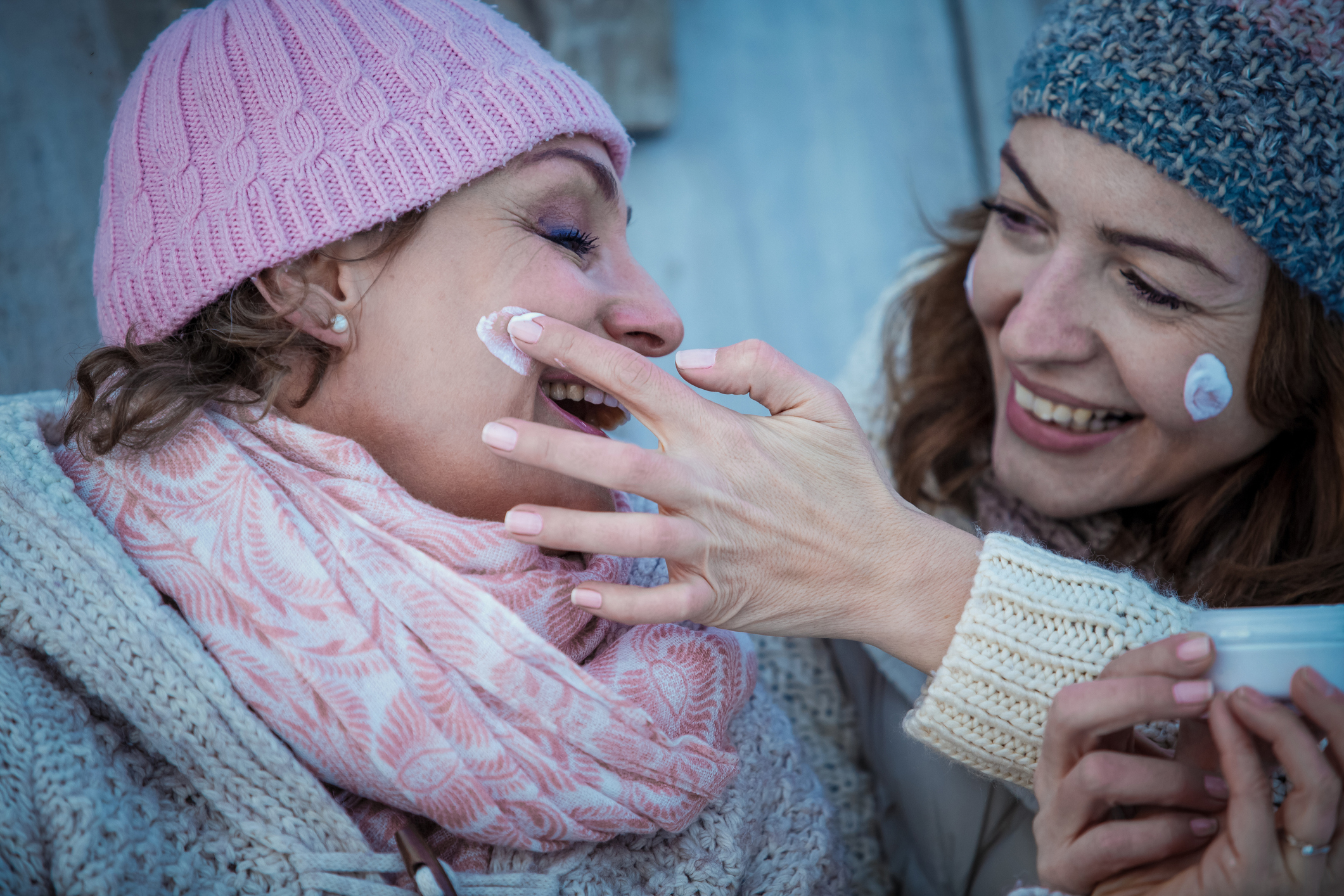 Close-up shot of a smiling women in warm clothing using facial cream outdoors.