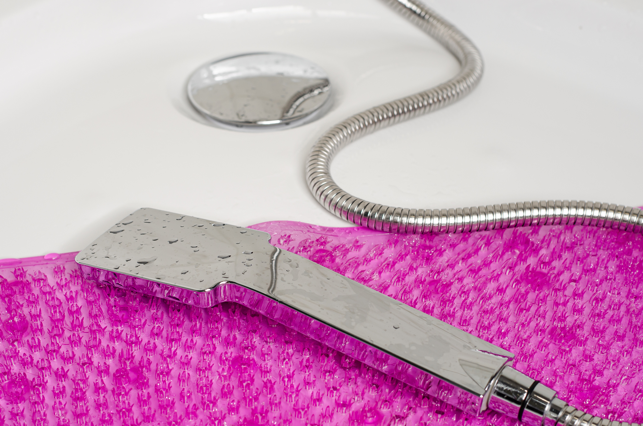 Purple anti slip rubber mat for bath and shower head lying in the shower stall. Close up, copy space.