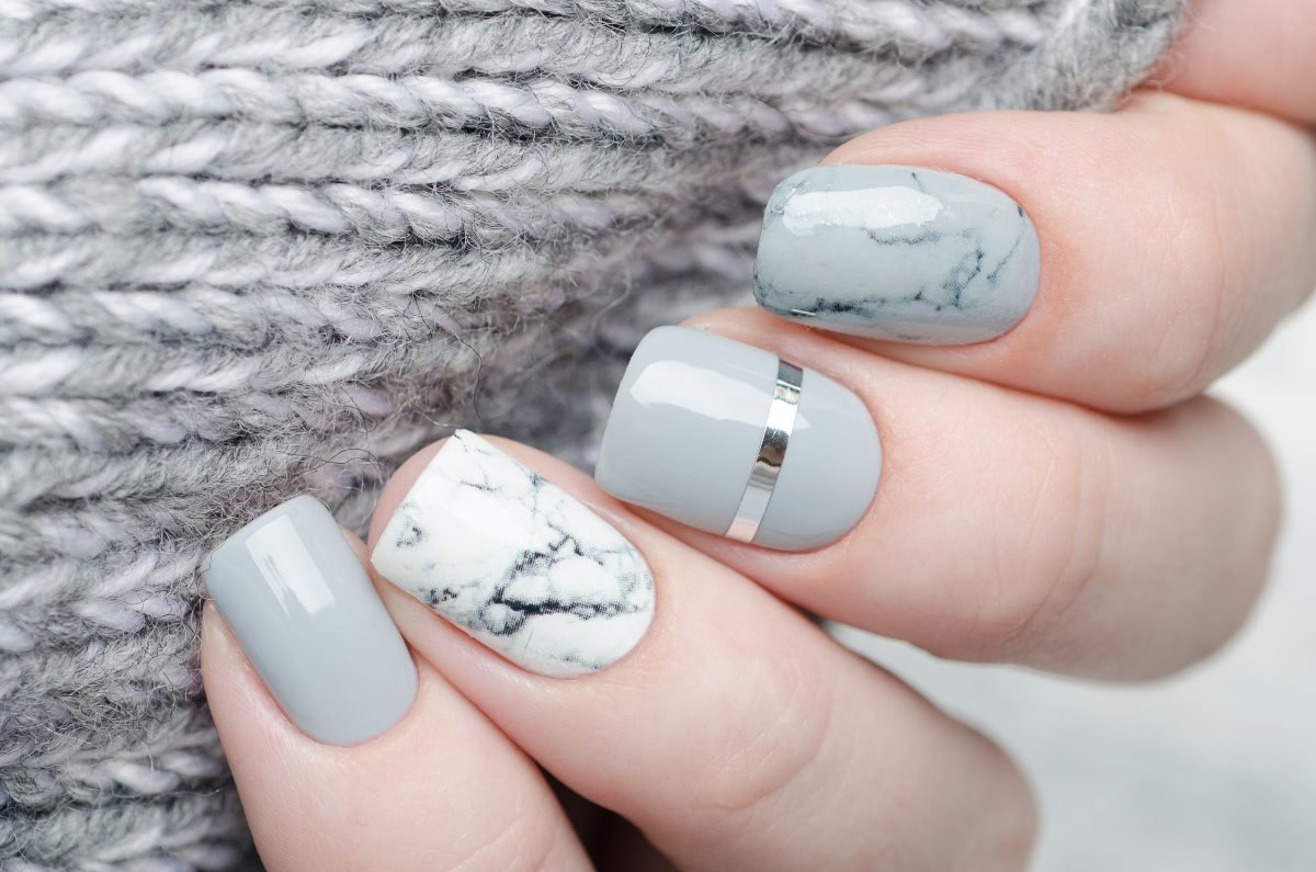 A gray and white marble manicure against a gray sweater