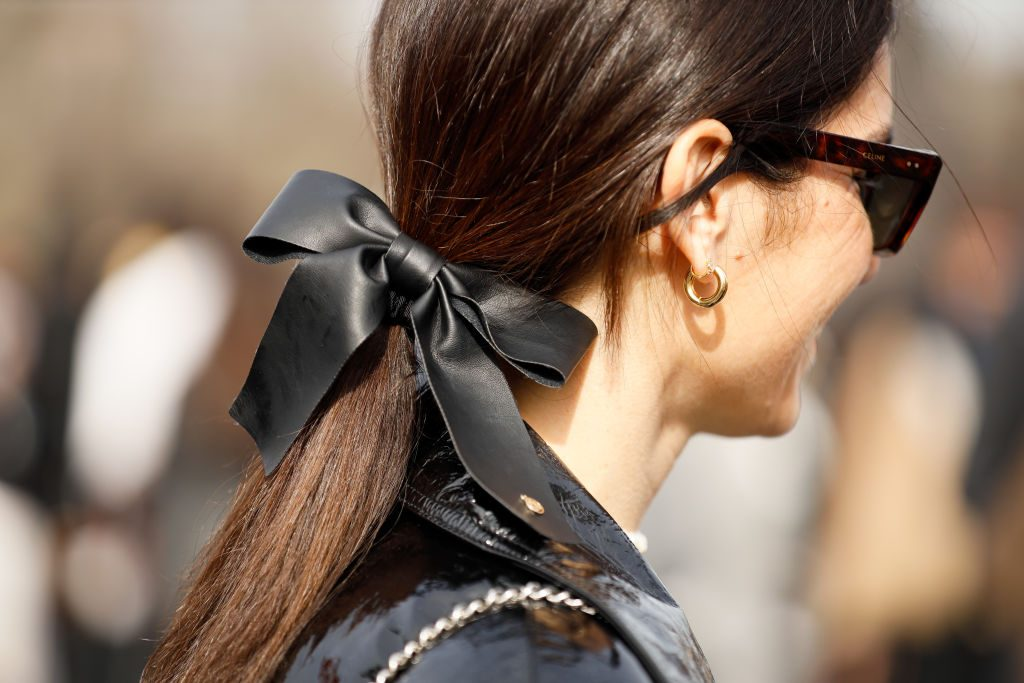 Woman wearing a hair bow in a low ponytail