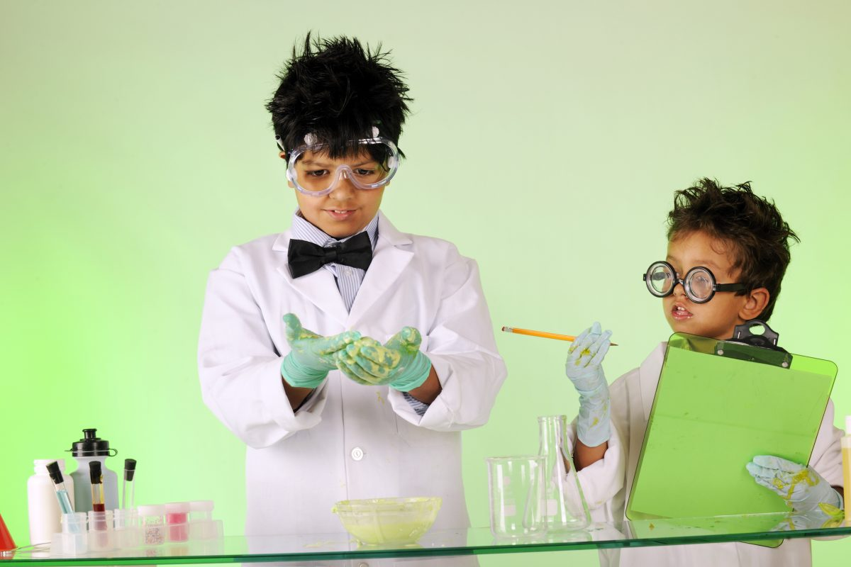 Two male children dressed as scientists experimenting with oobleck