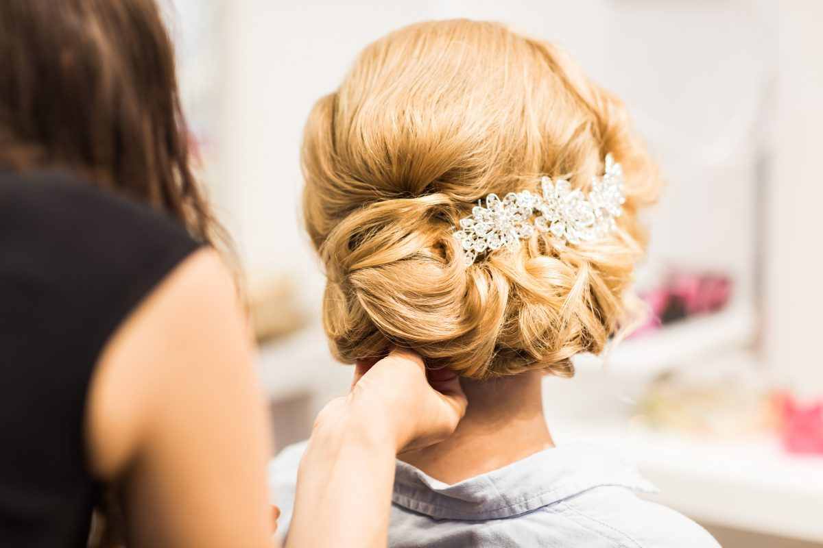 A woman in a hair stylist's chair getting a formal updo