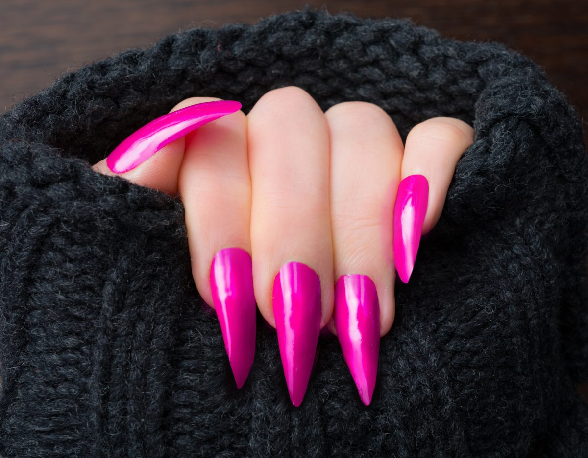 Stiletto-shaped nails painted a glossy vibrant pink shade