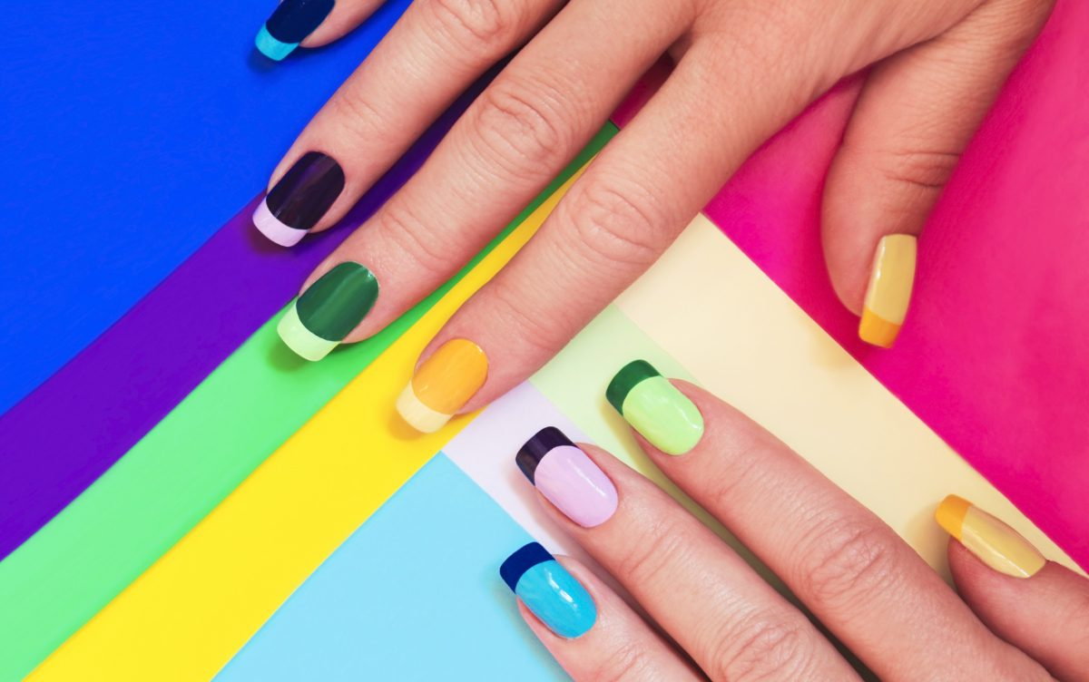 A colorful French-style manicure against a background of rainbow colors