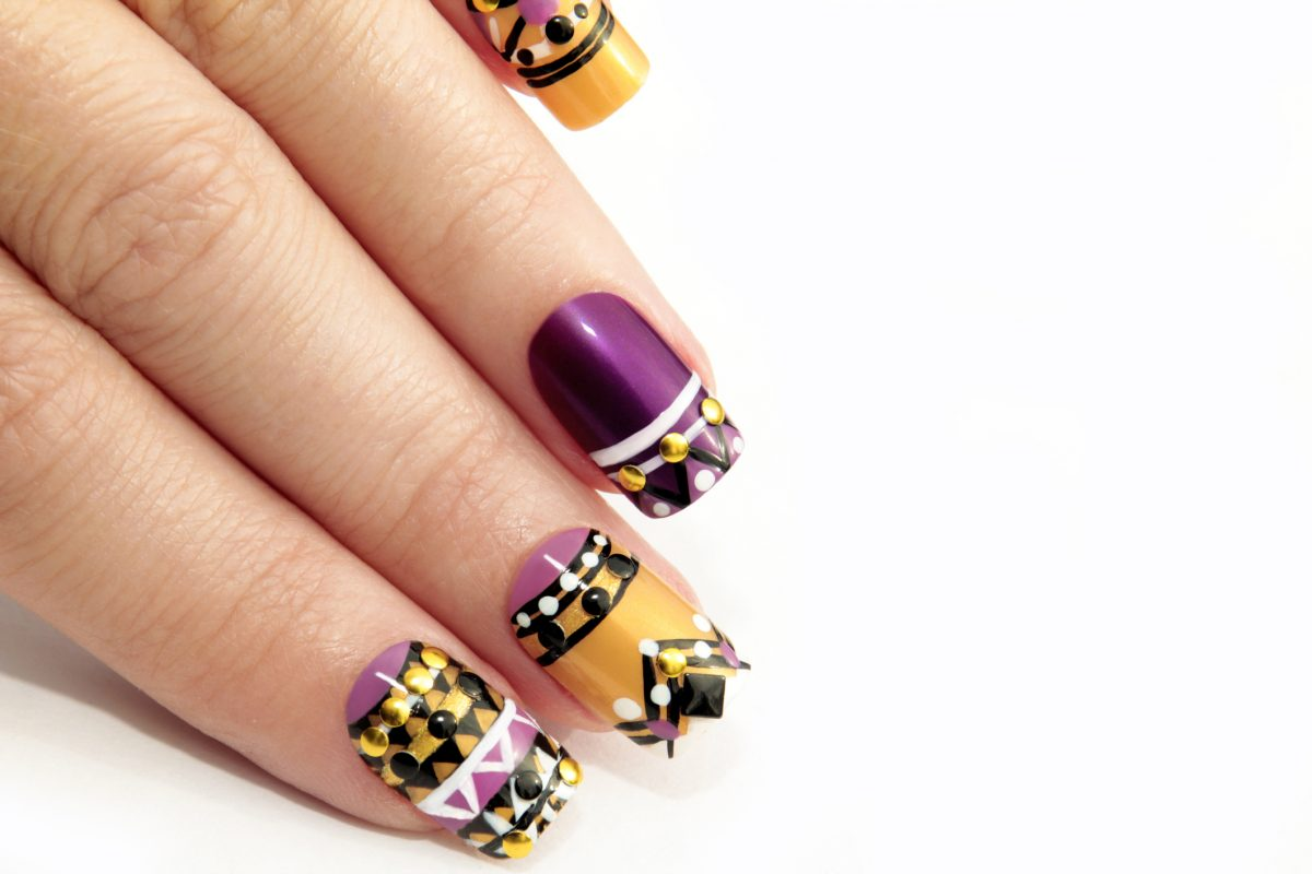 A very detailed graphic manicure in purple, gold, black, and white