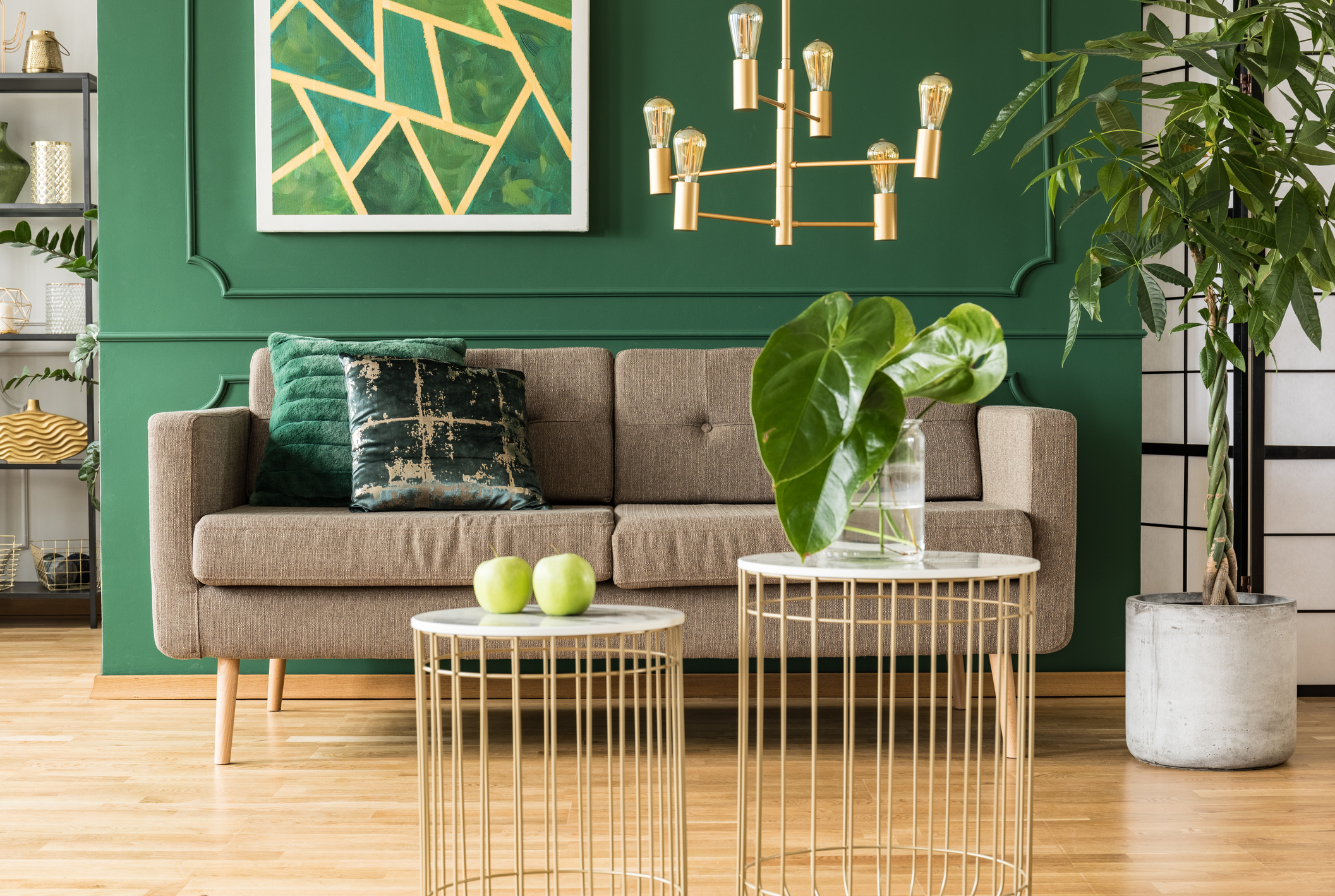 Elegant green and gold living room with comfortable brown sofa, coffee tables and golden chandelier