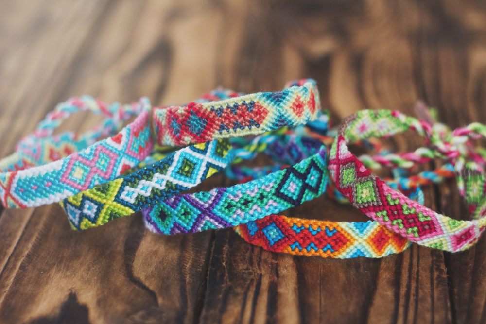 handcrafted colored friendship bracelets on wooden dark background