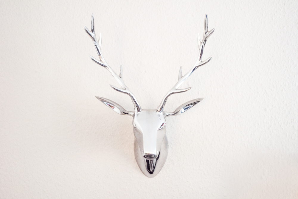 An artificial deer head is hanging on the wall