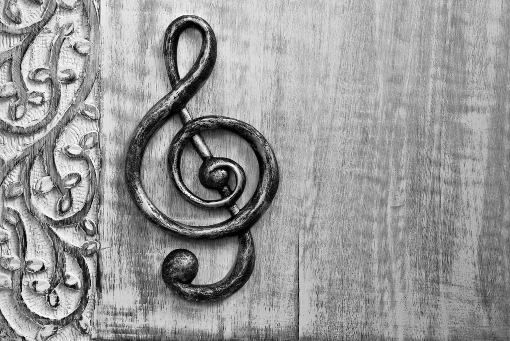 Black and white photo of metal treble clef on distressed wood with decorative carved border
