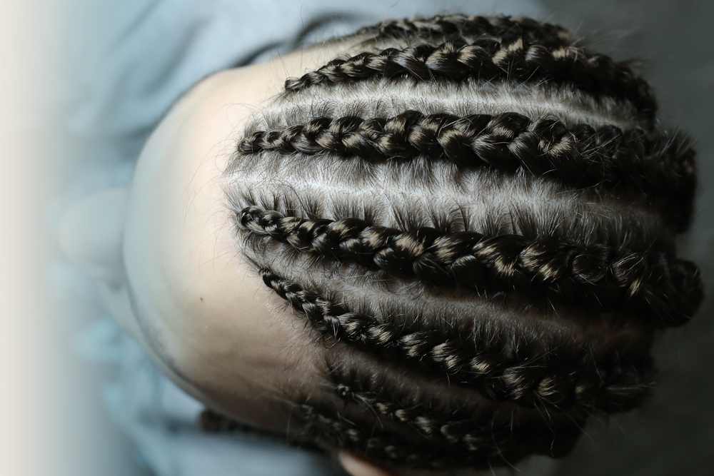 Corn rows with a large plate, a hairstyle for a young man, a frame, a teenager, long male hair braided in spikelets
